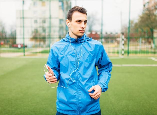 De man luistert naar muziek tijdens een training. een jonge man sport, rent op het voetbalveld. de man werkt in de open lucht. Premium Foto