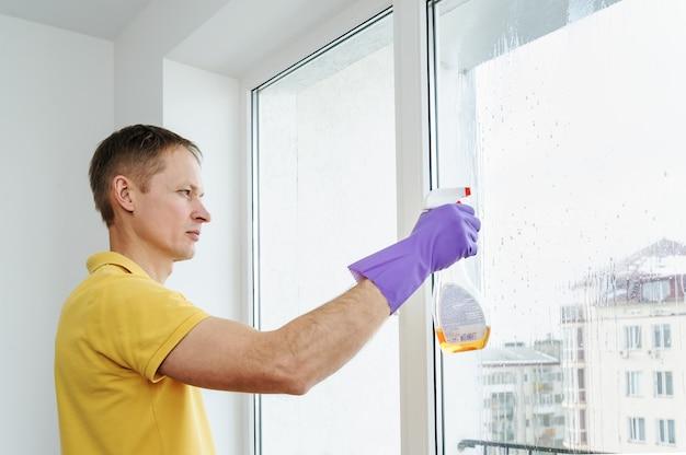 De man maakt de ramen in huis schoon Premium Foto