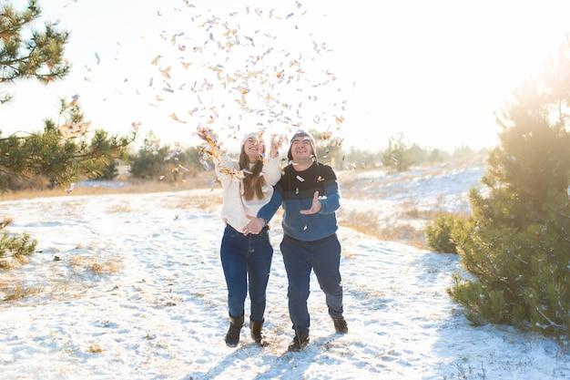 De man met het meisje gooit confetti in het winterbos Premium Foto