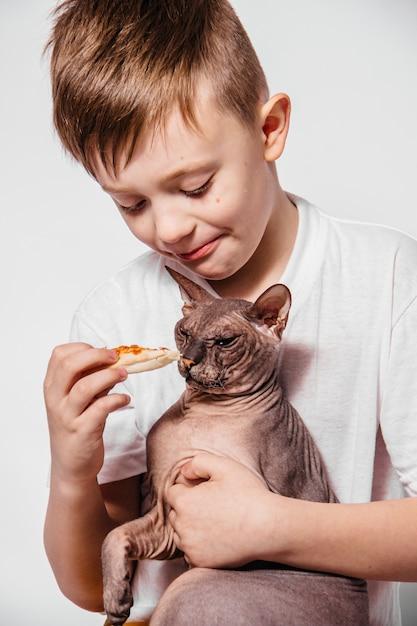 De man met veel plezier eet een stuk pizza en plaagt een kale kat op een witte muur Premium Foto