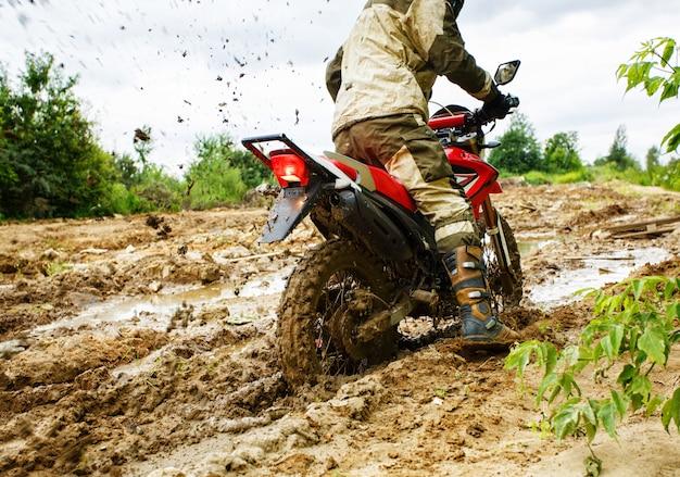 De man op een motorfiets rijdt door de modder Premium Foto