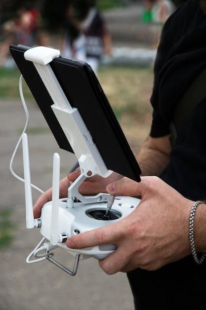 De man-operator houdt een bedieningspaneel voor de drone vast met een tablet Premium Foto