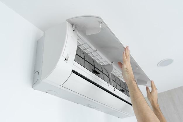 De man reinigt het filter van de airconditioner thuis van stof. Premium Foto