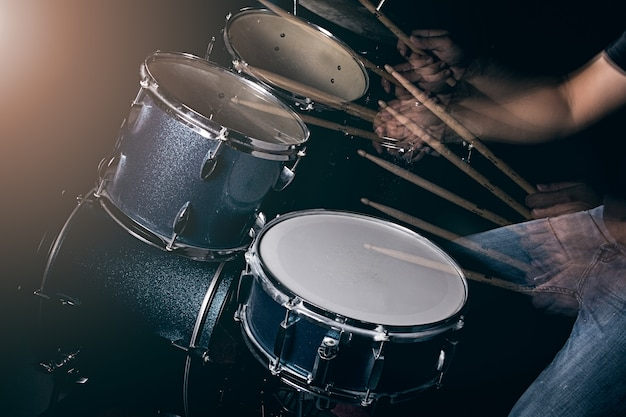 De man speelt drumstel bij weinig licht achtergrond. Premium Foto