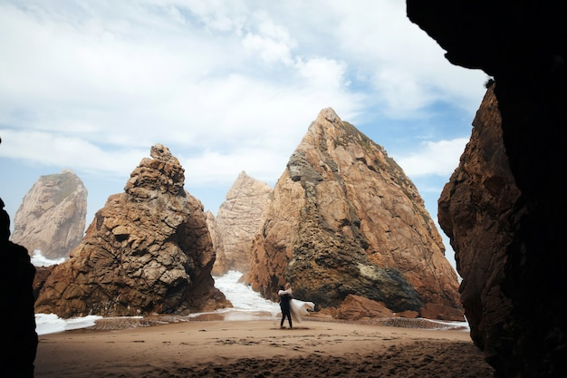 De man wervelt de vrouw en ze zien er erg gelukkig uit, een stel staat op het strand tussen de rotsen Gratis Foto