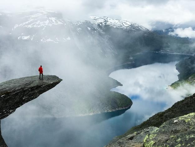 De man zit aan het einde van trolltunga voor de bergen Gratis Foto