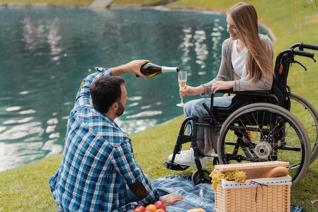 De man zit op een deken en giet een vrouw een glas champagne Premium Foto