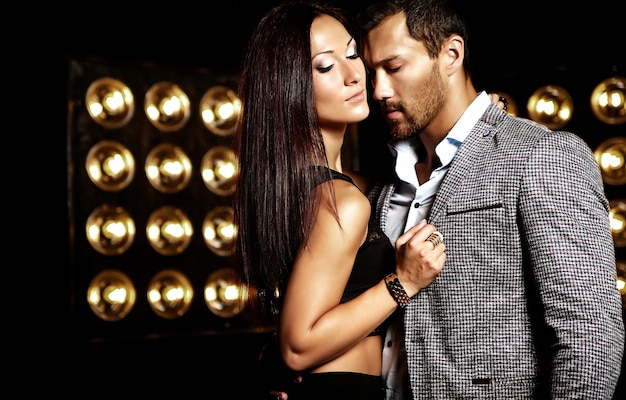 De manierfoto van de knappe elegante man in kostuum met het mooie sexy vrouw stellen op de zwarte achtergrond van studiolichten Gratis Foto