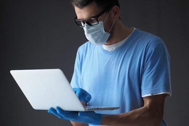 De mannelijke arts in medisch masker en handschoenen werkt in laptop. Premium Foto