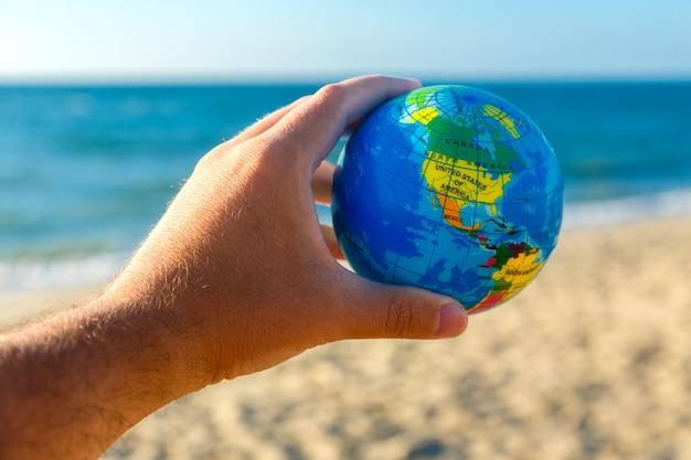 De mannelijke hand houdt bol van aarde op een kustachtergrond. reis concept. Premium Foto