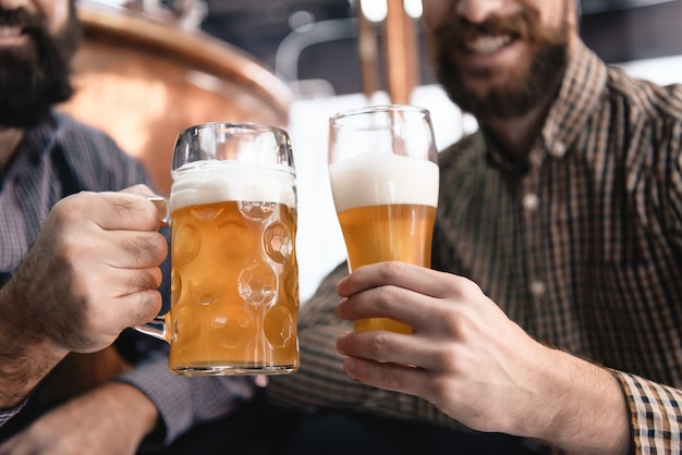 De mannelijke handen houden bier vers ale in glas en mok. Premium Foto