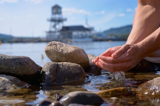 De mannelijke handen nemen schoon water van memphremagog-meer, provincie van quebec, canada op Premium Foto