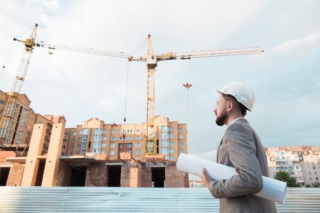 De mannelijke ingenieur draagt witte veiligheidshelm en houdt blauwdruk op bouwwerf Gratis Foto