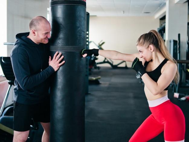 De mannelijke instructeur leidt jonge vrouw op om handstempels bij bokszak in de gymnastiek te doen Premium Foto