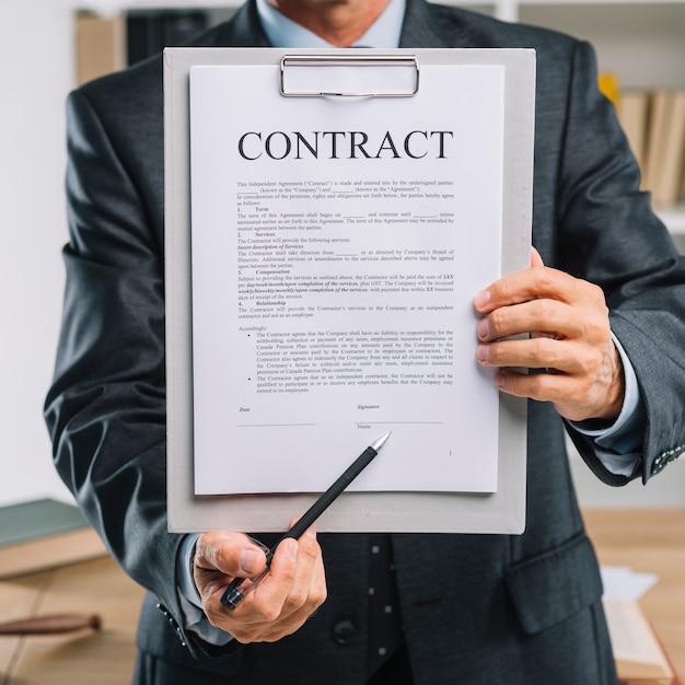 De mannelijke pen die van de handholding op handtekeningsplaats op een contractdocument richten Gratis Foto