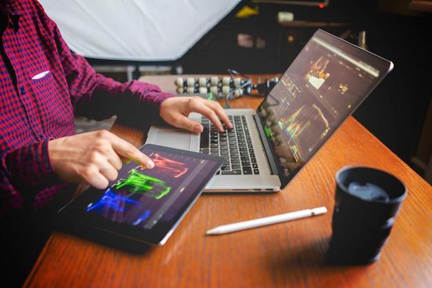 De mannelijke producent bewerkt video op zijn laptop in studio Premium Foto