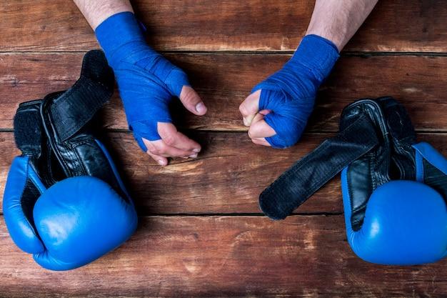 De mannen dient boksenverbanden en bokshandschoenen op een houten achtergrond in. conceptvoorbereiding voor bokstraining of gevechten. Premium Foto