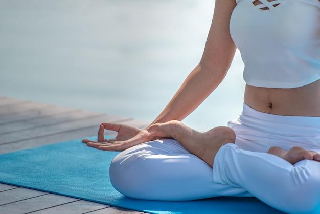 De meditatievrouw met lotusbloem stelt, sluit omhoog. Premium Foto