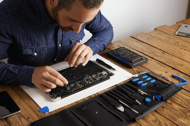 De meester gebruikt een gebogen esd-pincet om stof te verwijderen van elektronische borden van een kapotte, dunne computerlaptop om deze te repareren en weer aan het werk te krijgen Gratis Foto