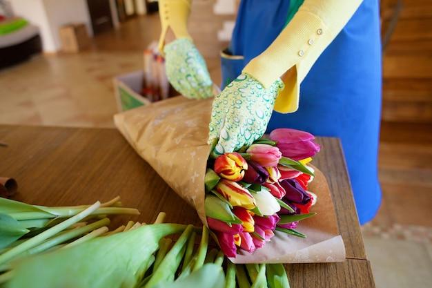 De meisjesbloemist verpakt mooie tulpen in een bloemenwinkel in kraftpapier-document Premium Foto
