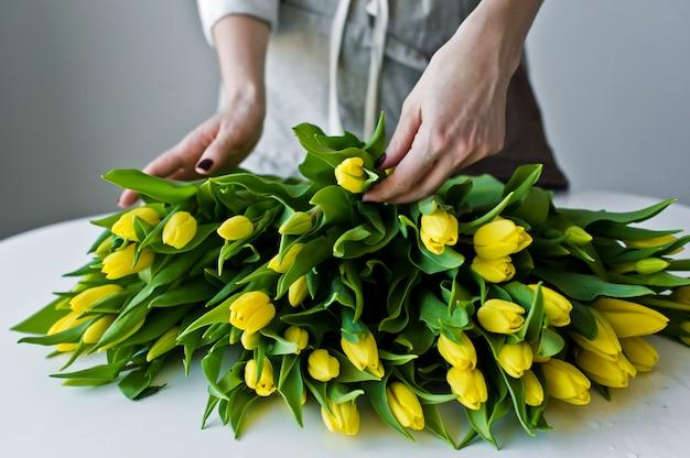 De meisjesbloemist zet op de lijst gele tulpen. Premium Foto