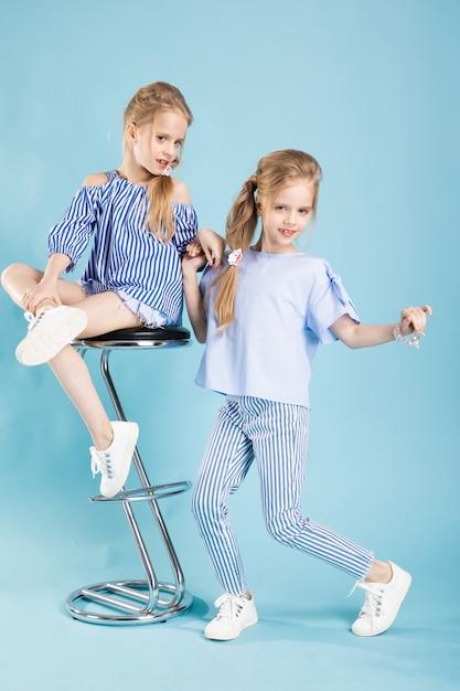 De meisjestweelingen in lichtblauwe kleren stellen dichtbij een barkruk op een blauw. Premium Foto