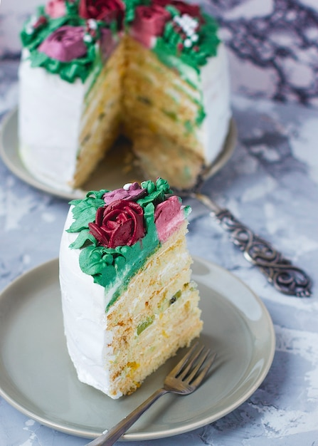 De melkachtige meisjescakeplak verfraaide groene bladeren en leliebloemen, cake die als bloemboeket wordt verfraaid, het decor van de de lentecake Gratis Foto