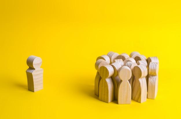 De menigte houten figuren van mensen staat in de verte en kijkt naar de rode man. slechte zaken Premium Foto