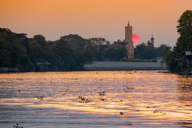 De mening van de avondrivier, zonsondergang en een kerk in phra nakhon si ayutthaya, thailand Premium Foto