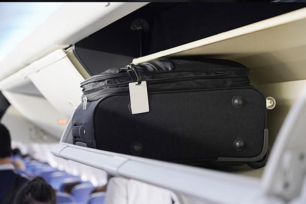 De mening van draagt bagage op luchtplank in de vliegtuigcabine Premium Foto