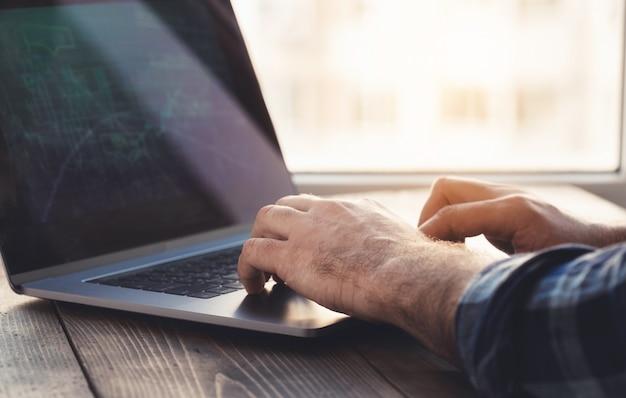 De mens analyseert en controleert de grafiek op laptop. thuiskantoor werkplek Premium Foto