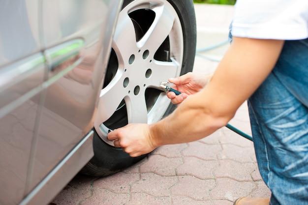 De mens controleert de bandenspanning van zijn auto Premium Foto