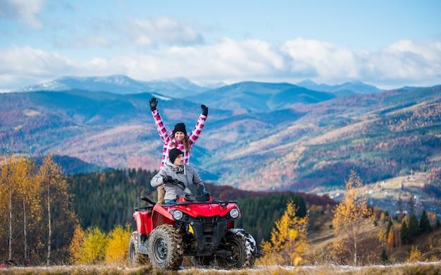 De mens die atv-vierlingfiets, vrouwenzitting achter hem drijven en hief omhoog haar handen op een bergweg op Premium Foto