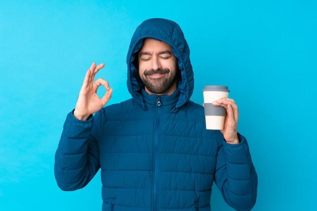 De mens die de winterjasje draagt en een meeneemkoffie over geïsoleerde blauwe muur in zen houdt stelt Premium Foto