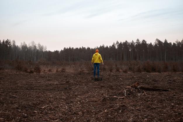 De mens die in een gele regenjas droeg, ziet het vernietigde bos na een technologische ramp Premium Foto