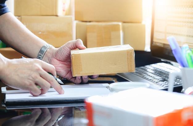 De mens die online aankooporder controleren en schrijft in de levering op pakketdoos die thuis kantoor werken. Premium Foto