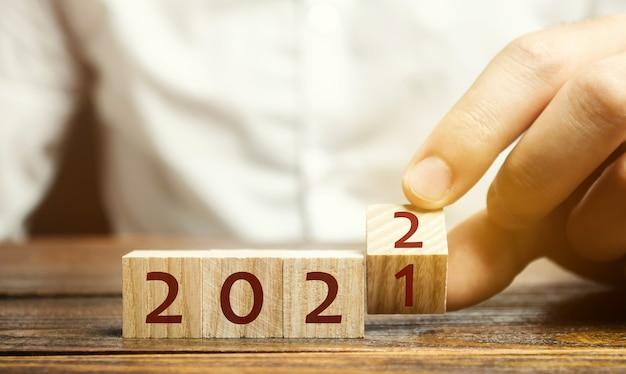 De mens draait een blok om en verandert 2021 in 2022. het nieuwe jaar begint. feestdagen en kerstmis Premium Foto