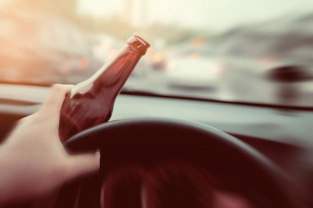 De mens drinkt bier terwijl het drijven van auto, rijdend in een staat van bedwelming, drink niet en drijf concept Premium Foto