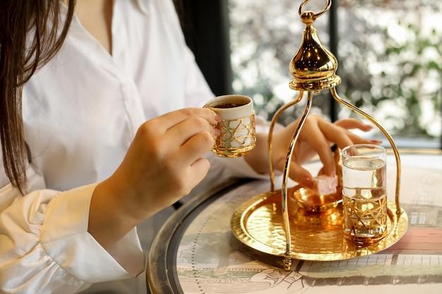De mens gaat turkse koffie in traditioneel de suiker zijaanzicht van het schotelwater drinken Gratis Foto