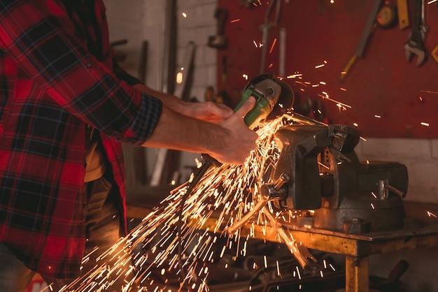 De mens gebruikt een hoekmolen terwijl het werken in reparatiewerkplaats. Premium Foto