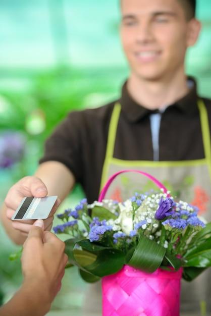 De mens geeft creditcard aan klant na aankoop. Premium Foto