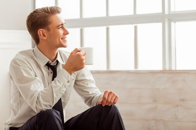 De mens glimlacht en houdt een kop terwijl het zitten in ruimte. Premium Foto