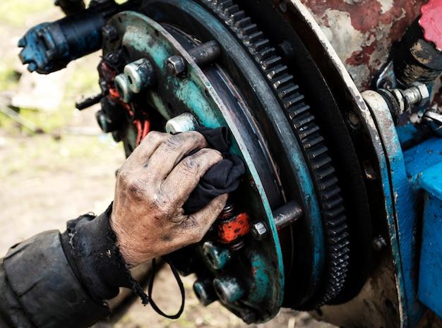 De mens herstelt motor van tractor, landbouwmachines. peiling, tandwielen, close-up. Premium Foto