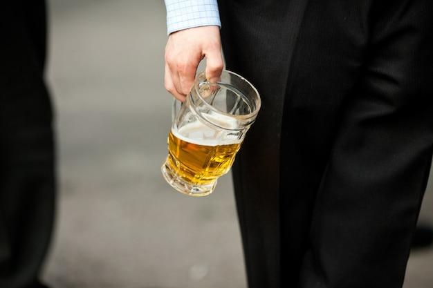 De mens houdt een bierkop in zijn hand Gratis Foto