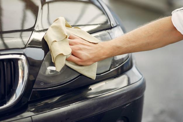 De mens in een wit overhemd veegt een auto in een autowasserette af Gratis Foto