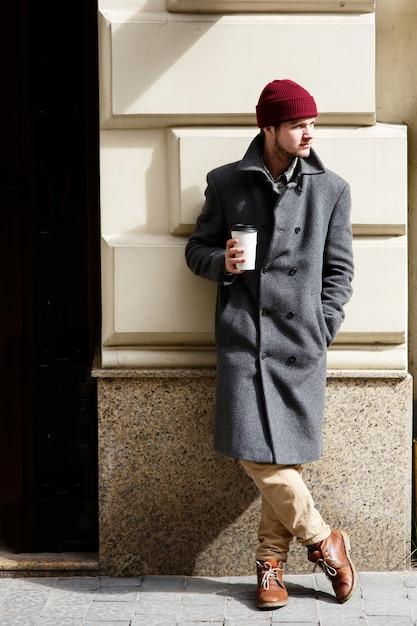 De mens in grijze laag bevindt zich met buiten kop van koffie Gratis Foto