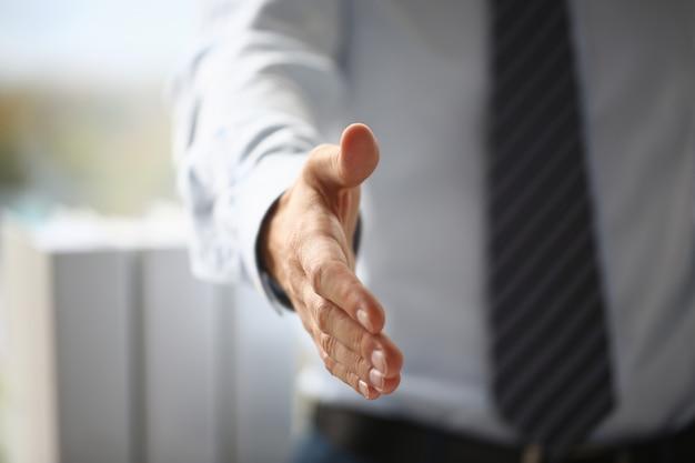 De mens in kostuum en band geeft hand als hallo in bureauclose-up Premium Foto