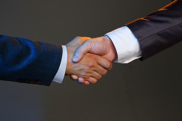 De mens in kostuum schudt hand als hallo in bureauclose-up Premium Foto