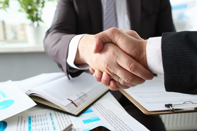 De mens in kostuum schudt hand zoals hallo in bureau Premium Foto