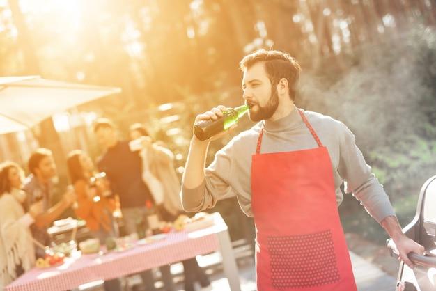 De mens in rode schort heeft pret en kookt voedsel en drinkt alcohol Premium Foto